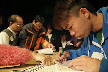 Shuxun Yu, right, 19, of Oakland, was given assistance filling out an application form during a health care enrollment event in March at the Oakland Asian Cultural Center (Photo by Eric Risberg/AP).