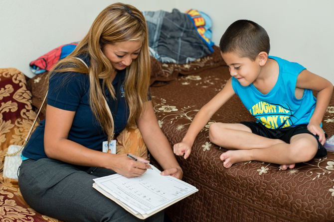 During a home visit, health educator Nunu Sixay sits down with 6-year-old Jovani Garcia-Vasquez and asks him to point out how his asthma felt that day (Photo by Heidi de Marco/KHN).