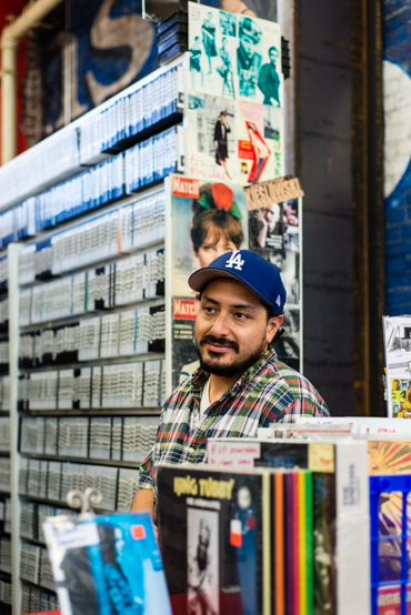 Miles Alva, 28, during his shift at Videotheque, a video store in South Pasadena. The television and cinema arts student says getting insured is not a priority and would rather deal with the penalty  (Photo by Heidi de Marco/KHN).