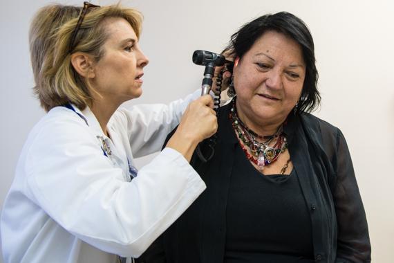 Nurse practitioner Wendy Davidson examines Teresa Martinez during an initial visit to QueensCare Health Center in Los Angeles (Photo by Heidi de Marco/KHN).