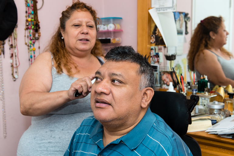 Frances Chuc brushes her husband's hair.  Jorge Chuc has been paralyzed for more than 30 years and needs full-time care from his wife (Photo by Heidi de Marco/KHN).