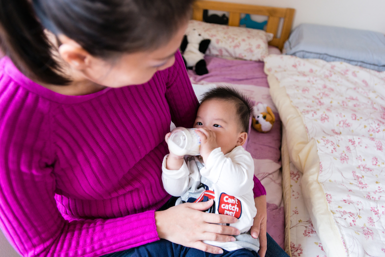 Cecily Liu, 37, feeds her 6-month-old son Nolan Liu. She had trouble adding him to the Blue Shield insurance plan she purchased through the state health exchange (Photo by Heidi de Marco).