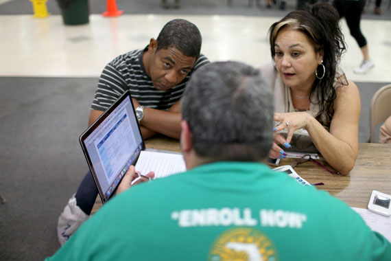 Jose Ramirez (L) and Mariana Silva speak with  Yosmay Valdivia, an agent from Sunshine Life and Health Advisors, as they discuss plans available from the Affordable Care Act at a store setup in the Mall of the Americas in Florida. (Photo by Joe Raedle/Getty Images)
