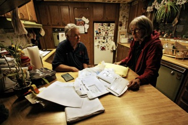 Dennie Wright and his wife Kathy go over health bills, related to care he got across the state line in Nevada. (Photo by Pauline Bartolone/Capital Public Radio)