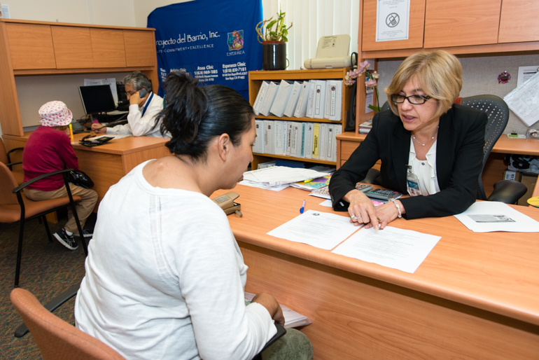 Enrollment counselor Brenda Barrios explains insurance options to Maria Lara, 39, an undocumented immigrant from Mexico, at El Proyecto Del Barrio Family Health Care Clinic signed up for My Health LA. Lara had a baby 6 months ago and hasn't seen a doctor since  (Photo by Heidi de Marco/KHN).