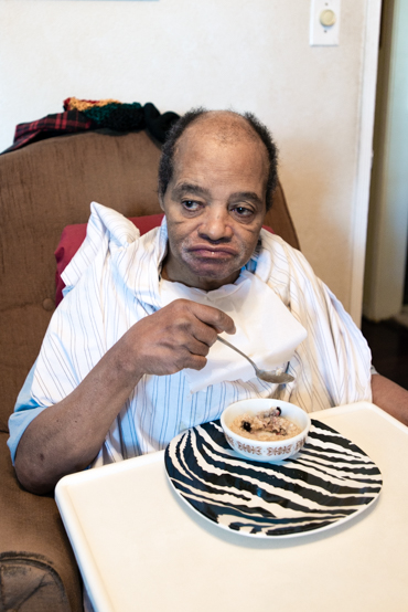 Charles Massengale can eat by himself, but needs help with everything else. The former tree trimmer has severe brain damage from a 30-foot fall, as well as dementia, diabetes and high blood pressure (Photo by Heidi de Marco).