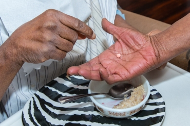 Charles Massengale takes his medicine one at a time during meals (Photo by Heidi de Marco/KHN).