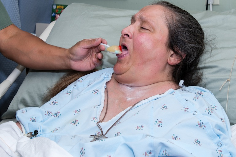 Toni Giusto, 54, takes a pill with her applesauce, administered by her night nurse (Photo by Heidi de Marco).