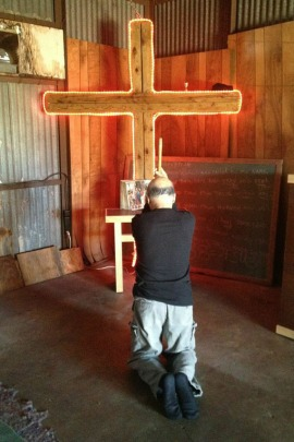 Bart Franco, 65, prays in the church he created in his backyard garage. After difficulties shopping on his own last year, Franco used a licensed broker to buy health insurance for his family in 2015. (Carrie Feibel/Houston Public Media)