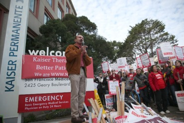 National Union of Healthcare Workers president Sal Rosselli speaks to protesters during day one of a week-long demonstration outside of Kaiser Permanente hospital on January 12, 2015 in San Francisco, California. An estimated 2,600 Kaiser mental health workers in California are staged a week-long worker strike at Kaiser hospitals thoughout the state over claims of understaffing and long appointment waits for paitents at Kaiser mental health clinics.  (Photo by Justin Sullivan/Getty Images)