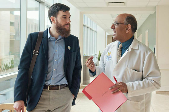 Dr. Raj Mangrulkar and medical student Jesse Burk-Rafel discuss the new medical school curriculum at the University of Michigan Medical School. (Photo by Leisa Thompson/For Kaiser Health News)