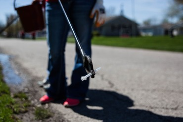 A volunteer holds a used syringe found a long a ditch line on Church St. in Austin, Indiana on April 11,2015. (Photo by Seth Herald/NurPhoto via AP Images)