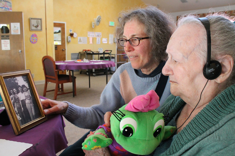Diane Schoenfeld, left, shows a family photo to her 97-year-old aunt, Lillie Manger. (Photo by Rachel Dornhelm/KQED)