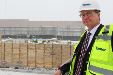 Cliff Kazmierczak of Turner Construction stands overlooking the construction site for the Cleveland Clinic's planned cancer outpatient center. (Sarah Jane Tribble/WCPN)