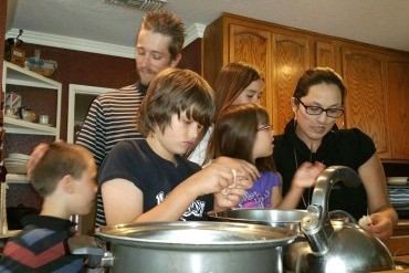The Packer family gathers in the kitchen to cook dinner. From left: Jacob, 8; Brian Sr. ; Brian Jr., 11; Savannah, 5; Scarlett, 10; and Stephanie. (Photo by Stephanie O'Neill / KPCC)