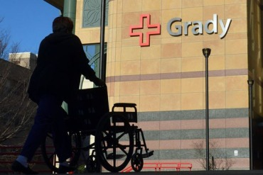 An employee returns a wheelchair to Grady Memorial Hospital after escorting a patient to their car Thursday January 16, 2014. (Photo by Brant Sanderlin/Atlanta Journal-Constitution)