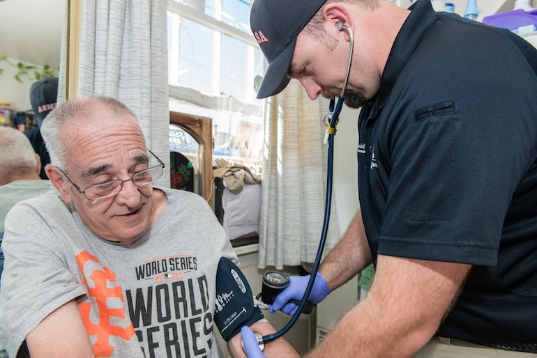 Paramedic Ryan Ramsdell checks 68-year-old Earl Mayes blood pressure during a home visit on March 26, 2015 in Sparks, Nevada. Ramsdell is part of a community health plan to help reduce avoidable emergency room visits by treating patients at home (Photo by Heidi de Marco/KHN).