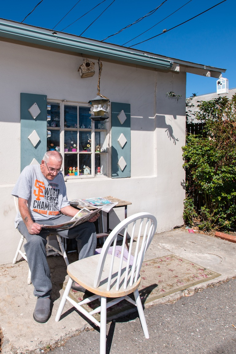 "Mayes returns to reading his newspaper in front of his one-bedroom house after his check up. Mayes is scheduled to have another surgery in May. ""I hope that works out good for me,"" he said (Photo by Heidi de Marco/KHN)."