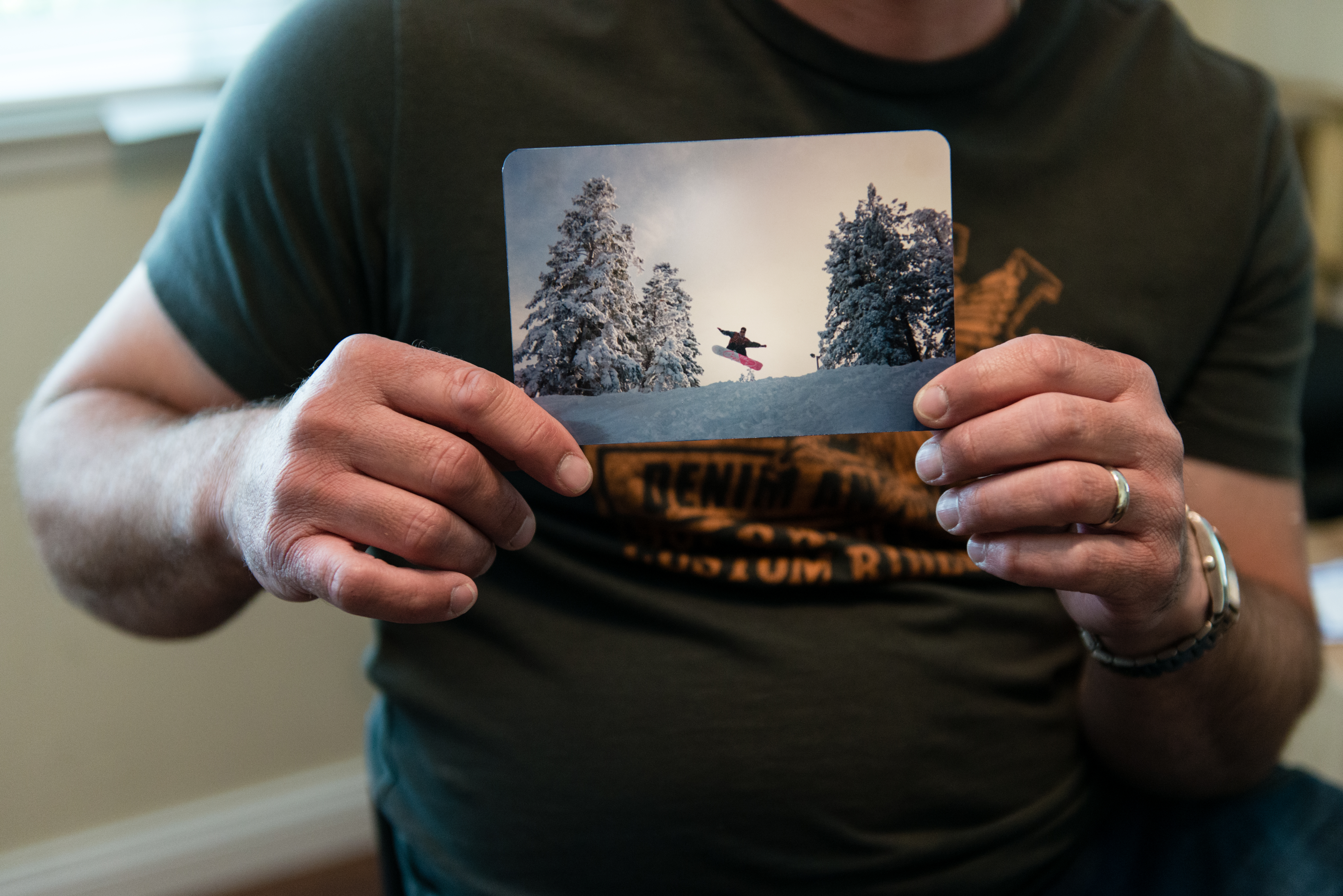 Anthony R. Orefice holds a photo of himself snowboarding at Mt. High in California before his accident.  Orefice says he is still physically active despite being paralyzed from the chest down (Photo by Heidi de Marco/KHN).