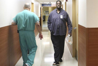 Vincent Adderly, right, a 46- year-old Miami Gardens man who is uninsured and diabetic, walks past an employee at Memorial Hospital West in Pembroke Pines on Thursday, May 28, 2015. (Photo by Marsha Halper/Miami Herald)