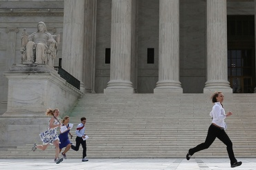 Television interns run to their reporters stationed outside after being handed the ruling on the Affordable Care Act, at the  Supreme Court June 25, 2015. The high court ruled that the Affordable Care Act may provide nationwide tax subsidies to help poor and middle-class people buy health insurance.  (Photo by Mark Wilson/Getty Images)