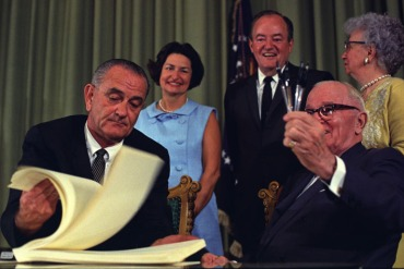 President Lyndon B. Johnson signed the bill creating Medicare and Medicaid at the library of former President Harry Truman, who was in attendance, on July 30, 1965. (Photo courtesy of Truman Library)