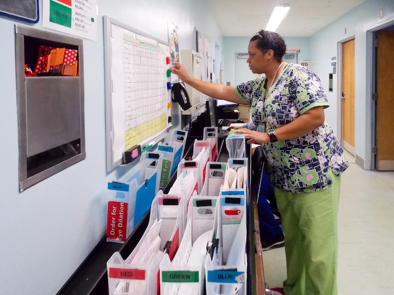 Nursing attendant Tracie Bell helps manage patients at the ophthalmology clinic at Los Angeles County Harbor-UCLA Medical Center on June 9, 2015. The hospital adapted Toyota's production system and created a color-coded system at the clinic to reduce wait times for patients. (Photo by Anna Gorman/KHN)