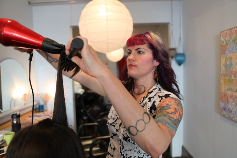 Mardi Palan cuts a client's hair at Gilly's Salon in Portland. Palan plans to use the $30,000 she could get for carrying twins, for a downpayment on a home.  (Photo by Kristian Foden-Vencil/Oregon Public Broadcasting)