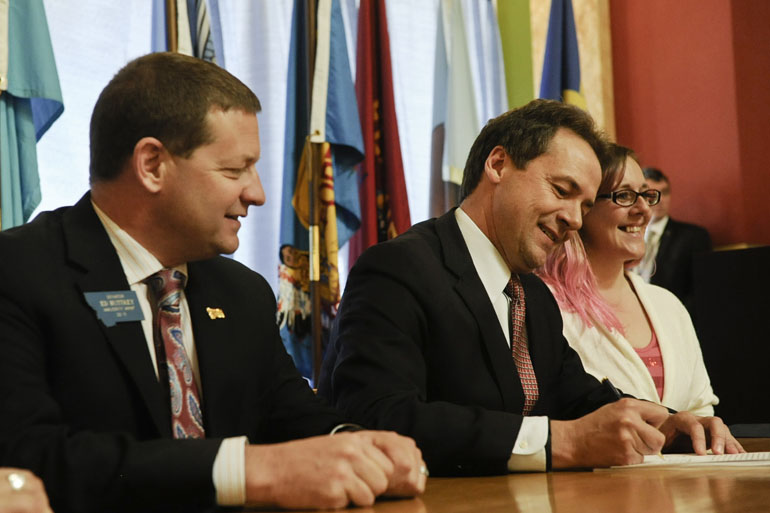 Democratic Gov. Steve Bullock, center, signs a bill to expand Medicaid to about 70,000 low-income Montanans in April. (Thom Bridge/Independent Record via AP)