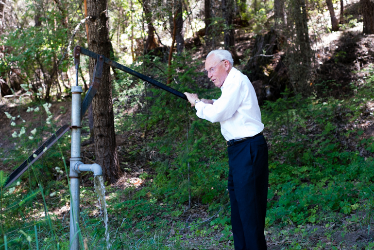 Dr. Earl Mercill pushes the lever of the water pump he built in the backyard of his house in Hayfork, California, on June 18, 2014. The 91-year-old takes daily walks around his 40-acre property daily (Photo by Heidi de Marco/KHN).
