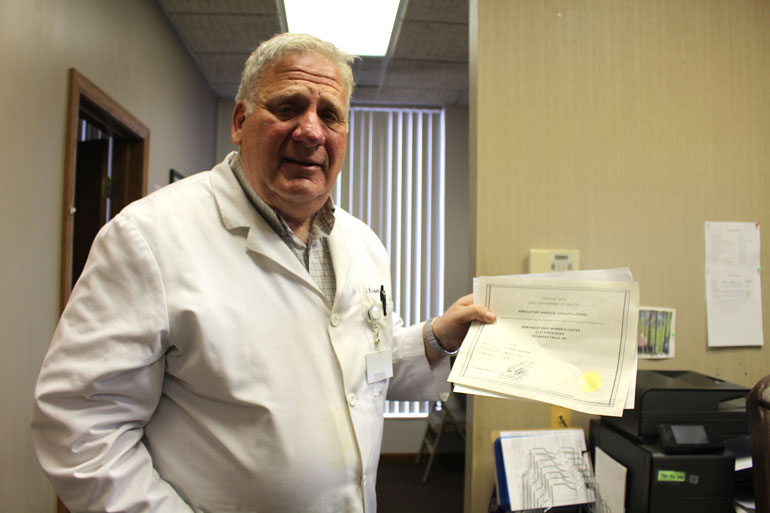 Dr. David Burkons, shows his ambulatory surgical center license that allows him to perform surgical abortions in his clinic outside Cleveland. (Photo by Sarah Jane Tribble/WCPN)