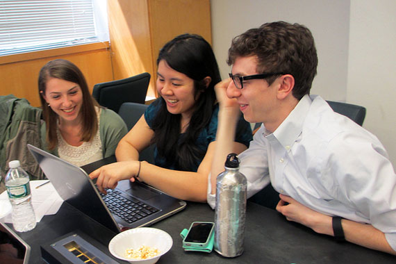 (Left to right) Christine Schindler, Mary Quien and Micah Timen hold a study session. Timen worked as an accountant before medical school; his database project tracked the relative costs of a hip replacement throughout New York compared to the relative costs of a fast-food hamburger.(Photo by Cindy Carpien for KHN/NPR)
