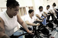 Female inmates take a spinning class