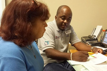 Harriet Cohen, 63, gets help enrolling in a health plan for under $7 a month at the Greenacres, Fla., library from navigator Abdius Pierre Cohen who lives in Boynton Beach, Fla. (Photo by Phil Galewitz/KHN)