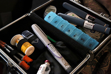 Smith keeps the tools for controlling her diabetes in this kit, which contains metformin, syringes, fast-acting insulin for daytime use and slow-release for overnight. (Photo by Lynn Ischay for NPR)