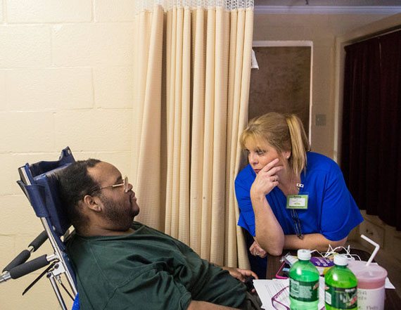 Lee Nalls talking with Kathy McCurry, a nurse. Medicaid does not reimburse nursing homes for the specialized equipment needed to care for severely obese patients. (Photo by Joe Buglewicz for The New York Times)