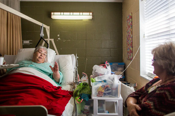 Wanda Chism, left, talking to Pam Bates, an administrator at Generations of Red Bay. Ms. Chism cannot walk on her own, and patients like her need to be repositioned every few hours to avoid dangerous pressure ulcers. (Photo by Joe Buglewicz for The New York Times)
