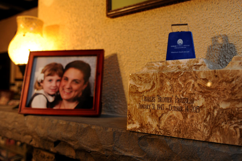 The cremated ashes of Charles Prozzillo are in an urn on the mantle in the Ft. Washington living room of his daughter Ashely Kearsley (in framed portrait with her now ten year old daughter, Chloe Kearsley) January 28, 2016. When Medicare stopped paying for his ambulance rides to dialysis a year ago, his family took him in their car. One day he fell and broke his hip, and died soon after. His grieving family blames the policy change. (Tom Gralish/Philadelphia Inquirer)