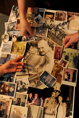 """The hands of his """"girls"""" touch a photo montage of the life of Charles Prozzillo made by his family for his memorial service. Clockwise, from left are hands of his granddaughter Chloe Kearsley, 10; daughter Ashely Kearsley; and his wife Roseann Prozzillo January 28, 2016. When Medicare stopped paying for his ambulance rides to dialysis a year ago, his family took him in their car. One day he fell and broke his hip, and died soon after. His grieving family blames the policy change. (Tom Gralish/Philadelphia Inquirer)"""