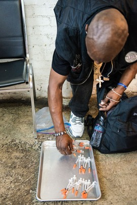 A man counts his used needles before turning them in for new ones. The Center for Harm Reduction in Skid Row distributes 1.2 million syringes each year. (Heidi de Marco/KHN)