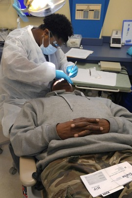 Reginald Rogers, 59, of Gary, Indiana, is examined at Kool Smiles of Gary, a dental clinic, by dentist Nicole Guyton. Rogers is in the Healthy Indiana Plan which he hopes Wil provide him with dentures. (Phil Galewitz/KHN)