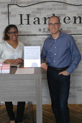 Tom Vanderheyden, CEO OF Harken Health, stands with a greeter at the Austell, Ga., clinic. (Phil Galewitz/KHN)