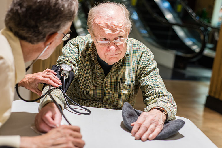 Dr. Aric Schichor checks Joe King's blood pressure at Mazza Gallerie in Washington, D.C., on Tuesday, March 15, 2016. Schichor is retired and volunteers his time at every mall walking session. (Heidi de Marco/KHN)
