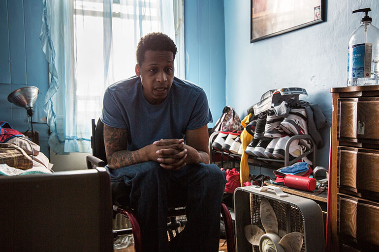 Vincent Berry, 28, who was paralyzed from a gunshot wound several years ago, lives with his grandmother in East Baltimore. Donnie Missouri, 58, a Johns Hopkins Hospital aide, is trying to help him find him stable, wheelchair-accessible housing. (Francis Ying/KHN)