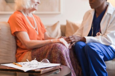 Senior woman holding hands with doctor in home