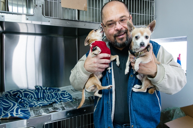 Elvin Quiñones, 55, visits his two chihuahuas at the Santa Fe Animal Hospital usually every other day. Quiñones put them in the kennel the day he became homeless. (Heidi de Marco/KHN)