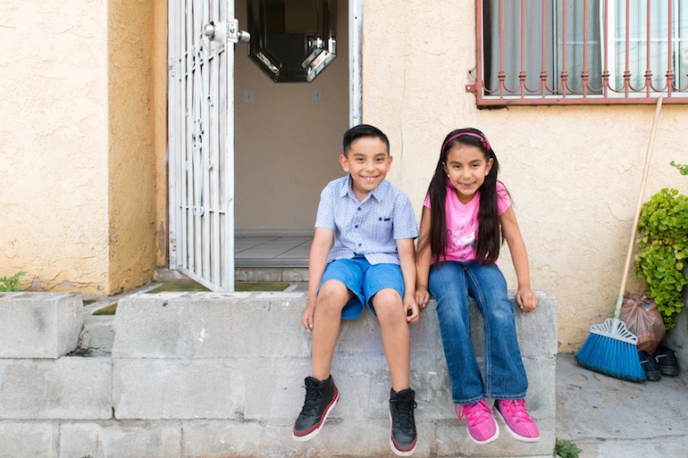 Siblings Benito and Stephanie sit on the front porch of their house in Los Angeles, Calif., on May 31, 2016. The children learned about earthquake preparedness at school and decided the porch would be the family's meeting place in case of an emergency. (Heidi de Marco/KHN)