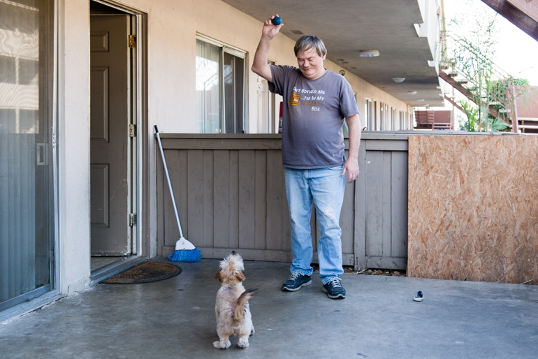 "Donald Meade plays with his puppy Scrappy in his apartment patio. ""If I lost this apartment, I would give Scrappy to my neighbors…I wouldn't want him to be stressed out living in the streets."" (Heidi de Marco/KHN)"