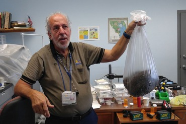 At the Broward County Mosquito Control office in Pembroke Pines, Fla., biologist Evaristo Miqueli holds a bag of thousands of dead mosquitos his agency has caught in 2016. (Phil Galewitz/KHN)