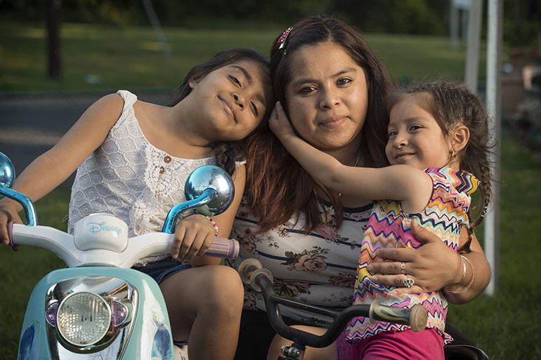 Cecilia Ramirez y sus dos hijas, Jenny Rodriguez-Ramirez, de 7 años, y Kimberly Gonzalez-Ramirez, de 3. Las niñas califican para el Medicaid porque nacieron en los Estados Unidos, pero su madre no por su status migratorio. (Doug Kapustin para KHN)